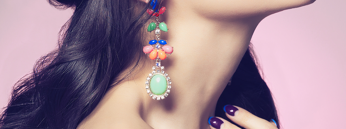 Fashion studio portrait of beautiful young woman with earring. Beauty and manicure. Jewelry and accessories